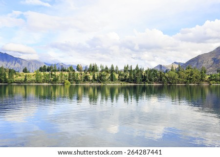 Lake Wakatipu green lakeshore under a cloudy sky - New Zealand - stock photo