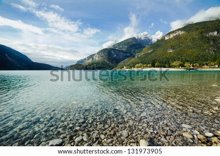 Lake with clear clean water on a background of mountains. There are many pebbles under water. Blue sky with light clouds. Snow on the mountain tops. - stock photo