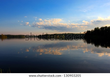 Lake with coasts covered with bushes and trees, quiet evening landscape - stock photo