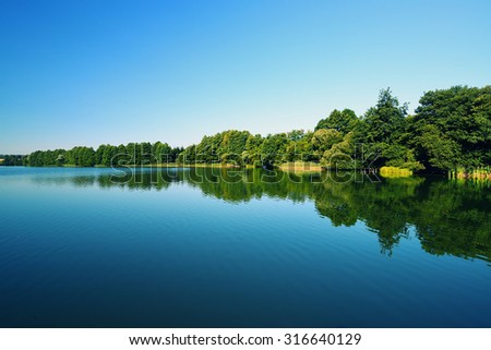 Lake with forest on the coastline. - stock photo