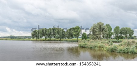 Lake with reeds and trees on the waterside and a cloudy sky above them. - stock photo