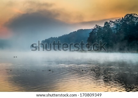 Lake with the fog at sunrise - stock photo