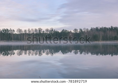 lake with water reflections in colorful autumn day with white clouds in blue sky- vintage effect