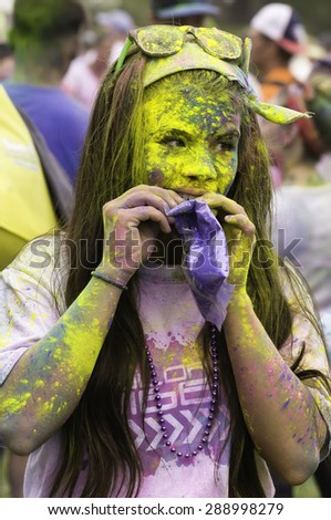 """LAKE ZURICH, ILLINOIS, USA - June 20, 2015: Vividly powdered on her face and arms, a young woman participant uses her teeth to open a bag of blue powder after a 5K """"fun run"""" in this suburb of Chicago. - stock photo"""