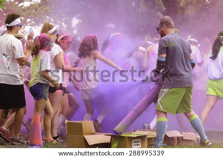 """LAKE ZURICH, ILLINOIS, USA - June 20, 2015: Young participants get blasted with blue powder at the start of a 5K """"fun run"""" in this northern suburb of Chicago. - stock photo"""