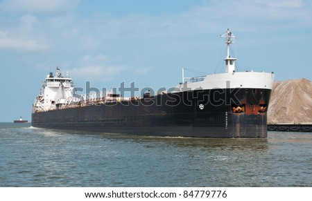 "Laker on the Cuyahoga River  A Great Lakes self-unloading bulk carrier ship (also known as a ""laker"") entering the Cuyahoga River from Lake Erie at Cleveland, Ohio - stock photo"