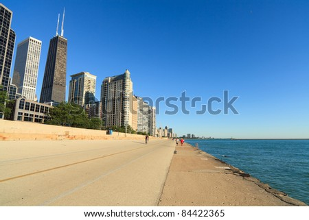 Lakeshore Trail in the early morning along Lake Michigan in Chicago with joggers and cyclists in the background. - stock photo