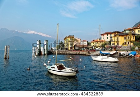 Lakeside scenery of Varenna, a beautiful village by Lake Como in Lombardy, Italy with view of sailboats parking at the pier, colorful houses by lakeshore & snow capped mountains in distant background - stock photo
