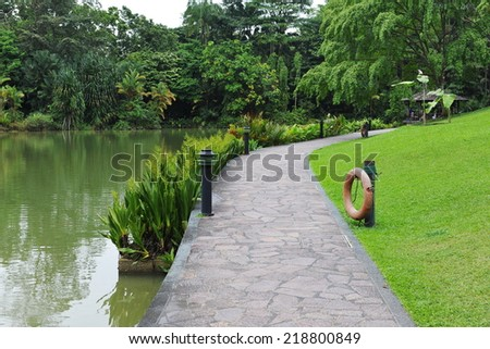 Lakeside Walkway in a Tranquil Garden - stock photo