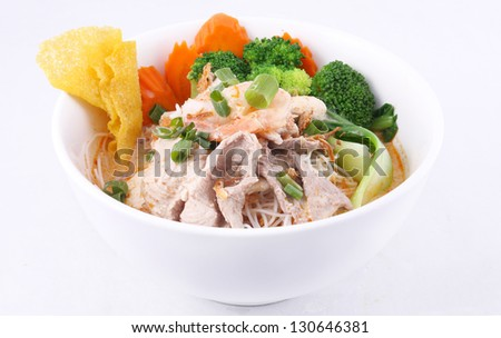 Laksa noodle soup with chicken, fresh vegetables and won ton on top