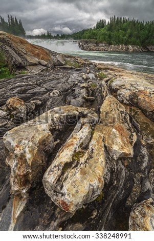 Laksfossen with textured foreground of volcanic rock - stock photo