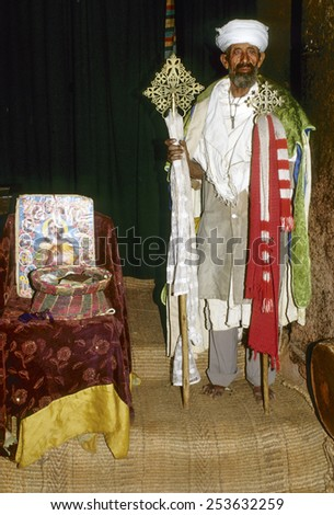 LALIBELA, ETHIOPIA - AUG 8, 2001: coptic priest is proud to present his church in Lalibela, Ethiopia. The coptic church dates back to 3d century AC in Ethiopia and is still vivid in the country. - stock photo