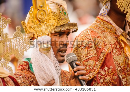 LALIBELA, ETHIOPIA - SEP 27, 2011: Unidentified Ethiopian religious man holds the golden cross and speaks during the Meskel festival in Ehtiopia. Meskel commemorates the finding of the True Cross