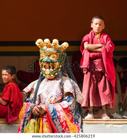 Lamayuru, India - June 17, 2012: monk performs a religious masked dance of Tibetan Buddhism, children monks carefully watching the ritual during the Cham Dance Festival in the Lamayuru monastery.