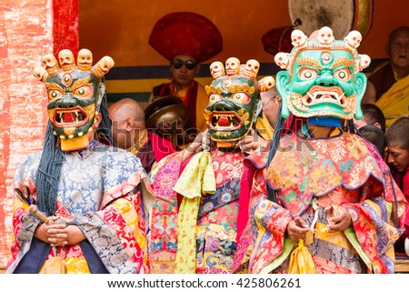 Lamayuru, India - June 17, 2012: monks perform a masked and costumed sacred dance of Tibetan Buddhism, another monks play ritual music during the Cham Dance Festival in the Lamayuru monastery, India. - stock photo