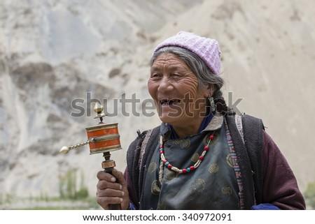 LAMAYURU, INDIA - JUNE 13, 2015: Unidentified buddhist old women during mystical mask dancing Tsam mystery dance in time of Yuru Kabgyat Buddhist festival at Lamayuru Gompa, Ladakh, North India - stock photo