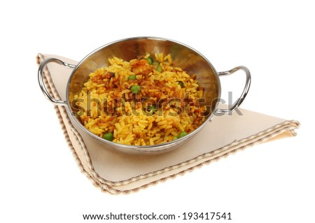 Lamb biryani in a balti dish on a seviette isolated against white - stock photo