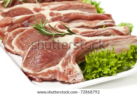 lamb chop ready for cooking, with fresh rosemary. Isolated on white. - stock photo