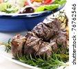 Lamb kebabs on rosemary skewers, with Greek salad behind. - stock photo