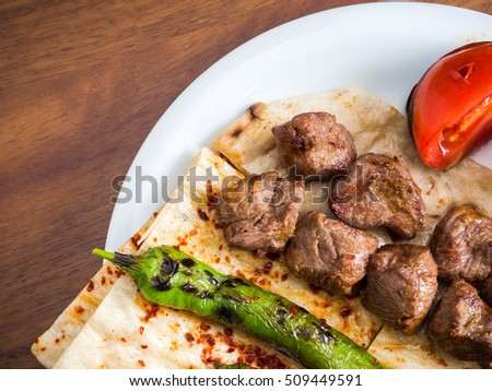 Lamb kebabs with flatbread, tomato and pepper