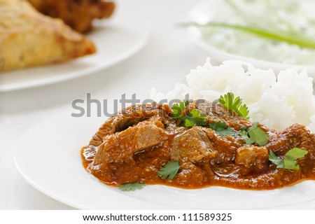 Lamb madras, a spicy meat curry garnished with coriander, with raita, samosa and bhaji behind. - stock photo