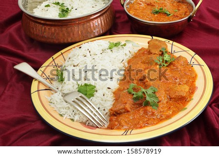 Lamb rogan josh, served with jeera (cumin) rice. A tilt-shift lens has been used to achieve huge depth of field. - stock photo