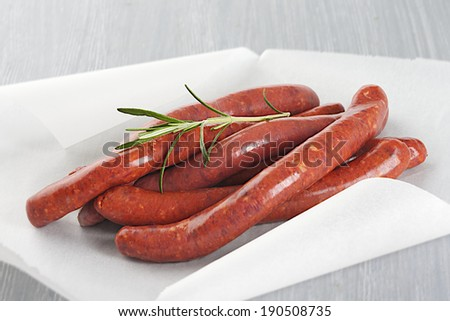 Lamb sausage with rosemary_string in baking paper - stock photo
