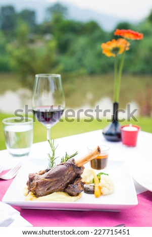 lamb shank and red wine outdoor restaurant table setting