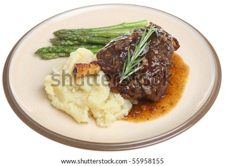Lamb shank with mashed potato and asparagus. - stock photo