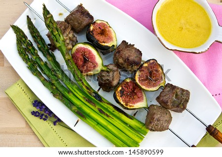 Lamb shashlik (grill) with figs, asparagus and tomatoes  - stock photo
