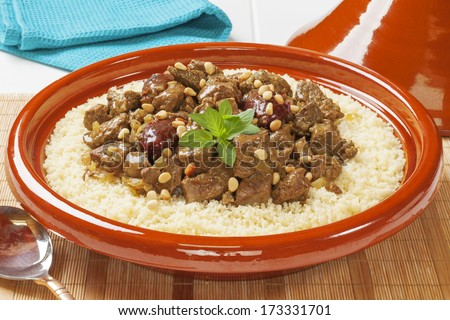 Lamb tagine with dates and pine nuts, served over couscous. - stock photo