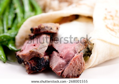 lamb wrap in a soft homemade flatbread with coconut rice and garlic fried beans - stock photo