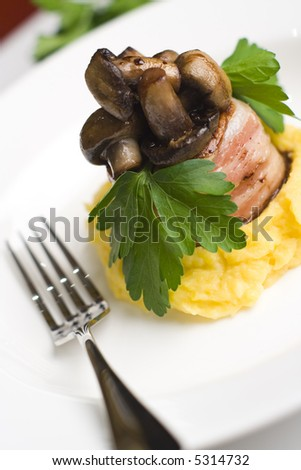 Lamb wrapped in bacon served with button mushrooms on butter pumpkin and potato mash. Garnished with flat leaf parsley. - stock photo