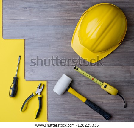 laminate and tools with a yellow helmet - stock photo