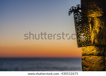 Lamp at sunset with view on sea - stock photo