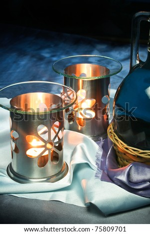 Lamp for aromatherapy with candles lit and breath-taking background. - stock photo