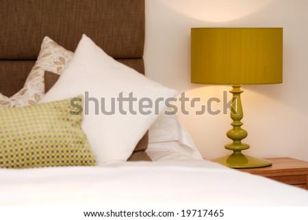 Lamp in brown-green designed bedroom - stock photo