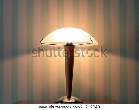 Lamp in front of a wall. Striped wallpaper. - stock photo