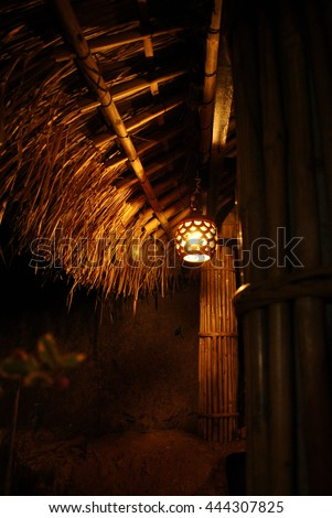 Lamp light orange under thatched roof