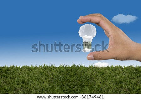 Lamp made of clouds in hand on sky. Ecology conception.Blue sky.
