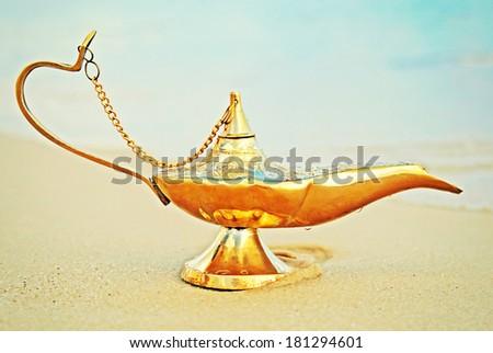 Lamp of Aladdin on beach - stock photo