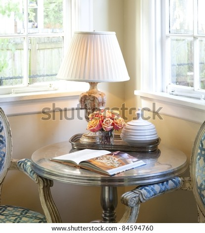 Lamp on a table with flowers and a book near a window in a corner - stock photo