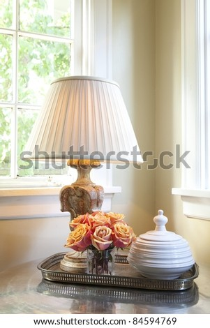 Lamp on a table with flowers near a window in a corner - stock photo