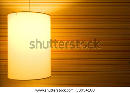Lamp on a textured wallpaper shining. Including copy space. - stock photo