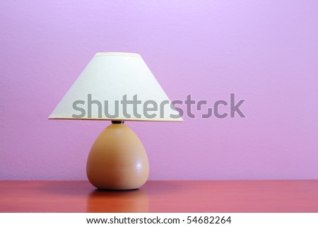 Lamp on a wooden table against purple wall - stock photo