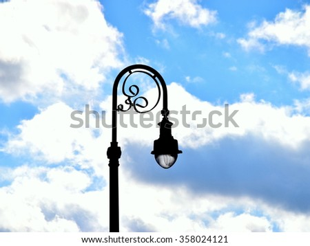 Lamp post against a blue sky full of clouds - stock photo