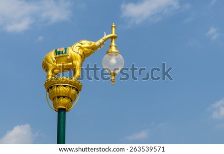 Lamp post in shape of golden elephant against blue sky, Thailand. - stock photo