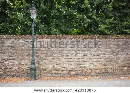 Lamp post street on brick wall background - stock photo