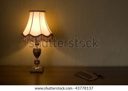 Lamp Shade, notebook and pen on a working table.