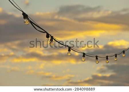 Lamp string hanging against a goldish sky background - stock photo